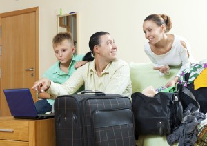 Middle-aged couple with teenage son reserving tickets and packin